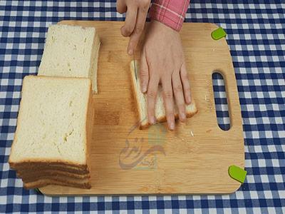 بریدن کناره های نان برای کیک مرغ و گردو