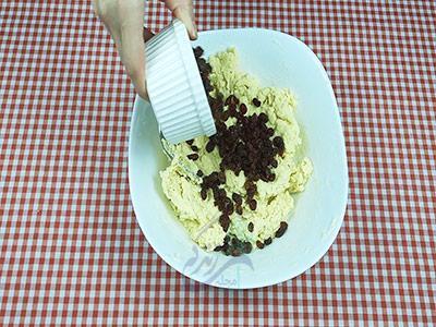اضافه کردن کشمش به مواد برای تهیه شیرینی کشمشی