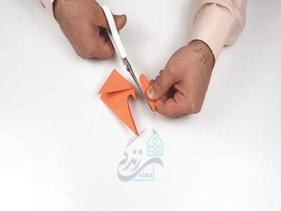 بریدن کاغذ برای ایجاد دم و باله ماهی در کاردستی ماهی با کاغذ رنگی