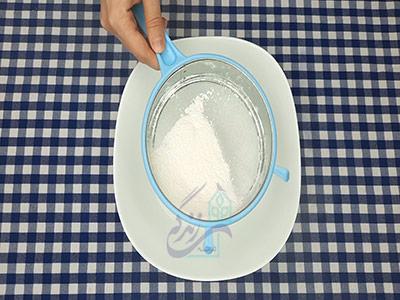 الک کردن پودر قند برای طرز تهیه شیرینی نخودچی خانگی