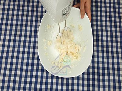 هم زدن پودر قند و روغن برای طرز تهیه شیرینی برنجی