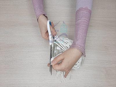 مرتب کردن نخ ها با قیچی در بافت مکرومه روی شیشه