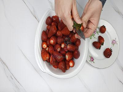 جدا کردن قسمت سبز توت فرنگی در طرز تهیه مربا توت فرنگی