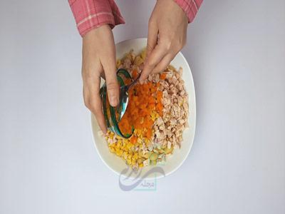 اضافه کردن هویج پخته شده به مواد در طرز تهیه سالاد ماکارونی