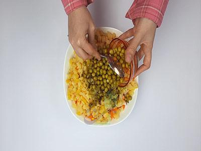 اضافه کردن کنسرو نخودفرنگی به مواد در طرز تهیه سالاد ماکارونی