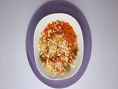 اضافه کردن هویج و تخم به مرغ به مواد در طرز تهیه سالاد روسی